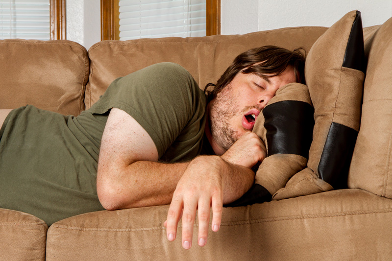 overweight man snoring on couch